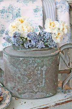 Bloemen in een oude gieter