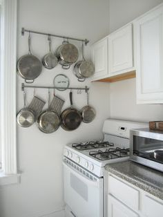 Hanging Pots + Pans Storage via T H E O R D E R O B S E S S E D photo by Laura Cattano