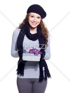 portrait of a young woman with her christmas present smiling. - Portrait of a young woman with her Christmas present smiling while standing over white background, Model: Brittany Beaudoin