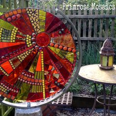 Art for the garden by Jacquie Primrose. Glass mosaic sculpture on metal and granite stand. Sunburst design.