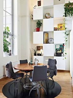 Appealing White Apartment Dining Room With Rounded Wooden Table And Black Chairs And Wall Mounted Cabinets And Shelves - Use J/K to navigate to previous and next images