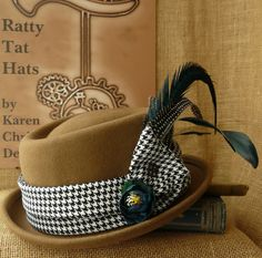 Butterscotch Pie - 56 to 57cms. A lovely little Steampunk Pork Pie hat that's caramel and teal blue shades combine beautifully with its dogstooth pattern fabric. Casual style but the co-ordinating hatpin and jaunty iridescent feathers set it apart.