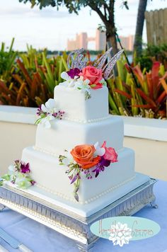 Simple wedding cakes don't have to be boring. Clean white fondant is wonderfully accented with  bright clusters of flowers. #Wedding #Cake