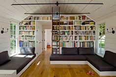 An amazing living room design. I love the cathedral ceiling with the books. Nice furniture - works well.