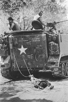 The body of a Vietcong soldier is dragged behind an American armored vehicle en route to a burial site after fierce fighting. (Kyoichi Sawada)