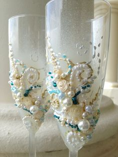 Beautiful wedding champagne glasses in ivory, aqua and teal, elegant toasting flutes with pearls and roses