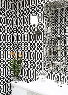 The repeat of this crisp black and white wallpaper's trellis pattern gives this small room an appeal that's Op Art-esque. When choosing wallpaper for a small powder room, don't be afraid of a geometric, bold or large-scale patterns.