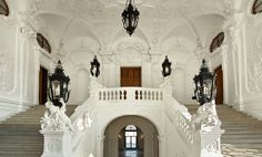 "This Sala Terrena hall (which is seen at the bottom) leads to the ""Prunkstiege"", the flamboyant Grand Ceremonial Staircase with white, richly carved stone and adorned black lamps."