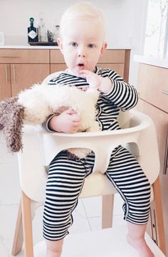 Cutie in her highchair wearing a black and white striped union suit by Goat Milk from Noble Carriage. Organic cozy and comfy, and snaps make for easy dressing. Perfect gift idea for minimalist new moms.
