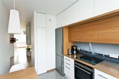 W tej kuchni jedną ze ścian w całości zabudowano szafkami z białymi frontami i drewnianymi blatami. Biel optycznie powiększa wnętrze a drewniane elementy ocieplają je. Z kolei czarno-biała fototapeta między szafkami dodaje wnętrzu finezji. W zestawieniu z nowoczesną płytą indukcyjną i lodówko-zamrażarką w modernistycznym stylu daje to ciekawą i funkcjonalną całość.