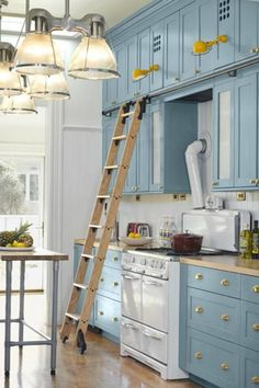 Stunning country blue kitchen cabinets with brass hardware and butcher block countertops.
