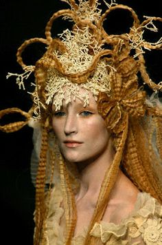 Jean Paul Gaultier fashion show with wild hair and hats.