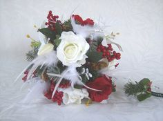 Hand wrapped bridal bouquet made with open red & open white roses, lilies, holiday pine, berries, pine cones, white feathers, & crystal gem sprays. Stems are wrapped with green ribbon secured with crystal pins and bow added. Crystal gem sprays and crystal gem pins add sparkle to the bouquet.