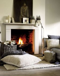 love the fuzzy floor pillow - Warm textiles and burning fire in this cozy fireplace setting by The White Company.