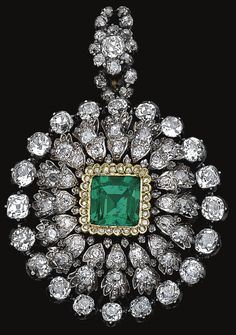 Emerald and diamond pendant/brooch, mid 19th century.               Of circular form, set at the centre with a cushion-shaped emerald within a scalloped frame of rose diamonds, further decorated with cushion-shaped and circular-cut stones, a few rose diamonds deficient, case, emerald setting may be a replacement. Sotheby's.