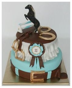 Equestrian style cake with rosette, horse shoes, stirrups, english / western belt, a showjumping horse and STILL room for ruffles! Perfection.