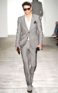 A single grey breasted suit with dual buttons and pointed lapels. Accessories sunglasses.