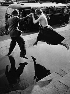 vintage everyday: A man gives a woman a helping hand as she takes a flying leap over a large puddle on the pavement, 1960