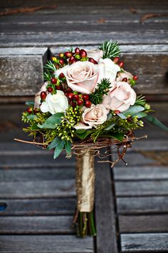The bouquets will be a combination of red spray roses, navy blue privet berries, red hypericum berries, seeded eucalyptus, and fresh rosemary, with the bridal bouquet featuring red garden roses and looped grapevine at the vase.