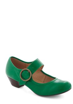 charming Mary Jane heels by Chelsea Crew. Their emerald-green exterior features a wide, bold strap with a decorative, antiqued golden buckle set atop a simple black heel, and the elasticized band allows you to quickly slip into these shoes with comfort and ease.