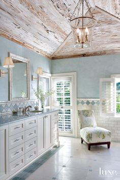 A cathedral ceiling clad in limed pecky cypress adds character to the main master bathroom, complete with a light fixture by Visual Comfort. Pale blue washes over the walls, countertops and marble details on the chair rail above tiled wainscoting by Waterworks. A Lee Industries slipper chair features a sea coral pattern by Cowtan & Tout. Paul Ferrante sconces light the vanity built by Hamlin Woodworks.