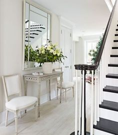 Period Swedish chairs flank an antique Swedish console table in the lovely, light foyer. - Traditional Home ®/ Photo:  Werner Straube / Design: Frank Babb Randolph
