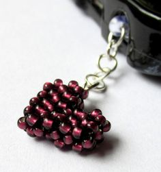 This little beaded dust plug is made into a cute heart charm using high quality burgundy Japanese seed beads and black beading thread. Attatched to the clear pluggy by a silver plated jump ring chain, it makes a great Iphone or Smartphone decoration while keeping the dust and lint from your pocket or purse out of your headphone jack!  $5.50