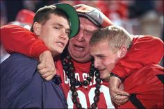 Hug it out, Ohio State fan. May you find comfort in your fellow enthusiasts as well as the jaunty hat/buckeye necklace combo. @Beth Nutkins