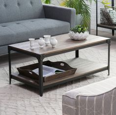 An industrial coffee table that adds an reclaimed distressed industrial style to your living space. It's built with black metal legs, warehouse-inspired corner brackets, and an engineered wood and bir
