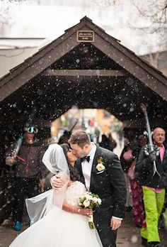 A post-ceremony kiss in the snow | @weddingsphotos | Brides.com
