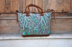 """Our Teal Alpaca Traveling Bag is made from a gorgeous Huipil (Mayan Shirt) from a place called """"Nebaj"""" in Guatemala. This huipil has complex weaving showing animals like alpaca, ducks, and other birds. In a beautiful teal color this bag couldn't get more unique. Complemented with 100% Guatemalan Brown Suede Leather."""
