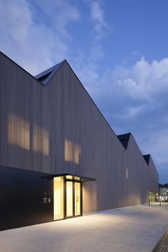 Facade. Vertical thin sticks done with light warm grey, almost beige, wood.. Festhalle Kressbronn