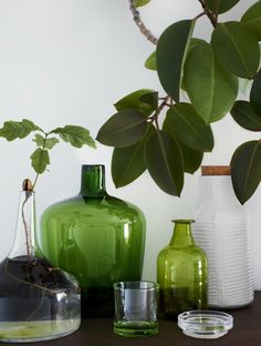 glass vases in clear, green and white combined with greenery.