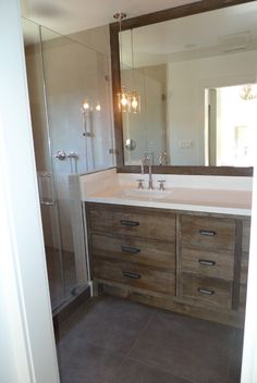 Glossy + Rustic Bathroom 2 with white walls and tile, glossy white countertops, rustic vanity and pendant lights in front of mirror - Mill Valley home by Tineke Triggs of Artistic Designs for Living