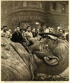 """Hungarian Revolution, 1956  photograph by Sandor Acs. The writing on the statue of Stalin translates as """"The Murderer of 25 Million People""""."""