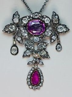 A mid-19th Century Pink Sapphire, Ruby and Diamond Pendant / Brooch. Of floral design, crafted in silver and 14K gold, set with one oval pink sapphire, one pear shaped ruby, old cushion- and old rose-cut diamonds. The jewel can be worn as a pendant or a brooch. marked with later French import marks. #Antique