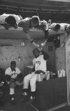 Giants baseball players Willie Mays (R) and Willie McCovey (L) in the dugout of the new Candlestick stadium. Photograph by Jon Brenneis. San Francisco, California, April 1960.