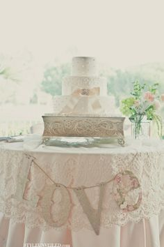 Cake table dressed in lace and Love banner with a silver square cake stand, flowers, and simply beautiful wedding cake in white with a blush pink ribbon and brooch   http://weddingdressblogimages.blogspot.com