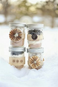 4 Mason jar packaging / gift wrap ideas. No Tutorial, just an inspiration pic. materials used are kraft paper, paper lace ribbon, ivory basting tape (correct term?), glittery yarn (center of paper flowers), old buttons (the kind on tweed sport jackets)