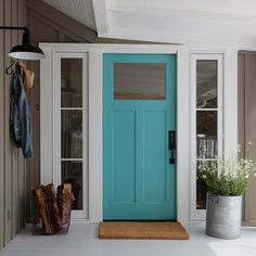 Chic cottage home features taupe siding framing a turquoise front door flanked by sidelights.