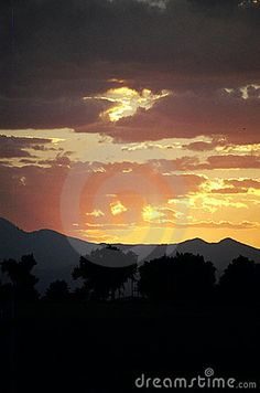 Bright clouds reflecting sunlight after sunset behind mountains, suggesting glowing images of angels.