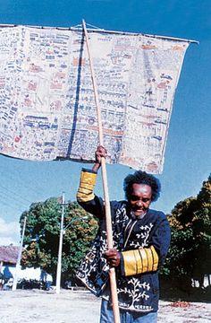 O XERIFE DO HOSPÍCIO  Bispo do Rosário veste um de seus mantos e carrega um estandarte na Colônia Juliano Moreira, na década de 1980. Ele transformou sua cela-forte em ateliê (Foto: divulgação)