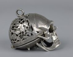 This Memento-Mori watch presented by Mary Queen of Scots to her attendant Mary Seaton, is from the 16th century.  The forehead of the skull is engraved with a figure of death between a palace and a cottage, and a quotation in Latin, 'pale death visits with impartial foot the cottages of the poor and castles of the rich'. (Horace)    http://thiswritelife.wordpress.com/