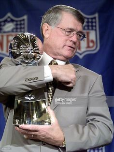 Atlanta Falcon's Coach Dan Reeves hugs the Vince Lombardi Super Bowl trophy after addressing the media at a press conference 29 January in Miami, FL. Reeves, still recovering from open heart surgery, talked about his team's preparation against the defending Super Bowl Champions' Denver Broncos in Super Bowl XXXIII 31 January.(ELECTRONIC IMAGE) AFP PHOTO/Stephen JAFFE