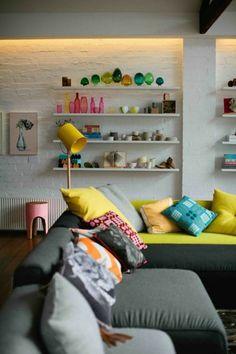 canapé gris, coussins colorés décoratifs, étagère en bois blanc, mur de briques blancs