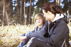 Mature woman taking a break with her son in a forest - Peter Muller/Cultura/Getty Images