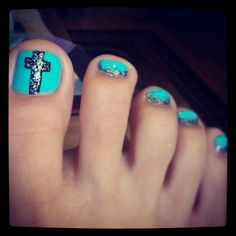 Cross nails with turquoise and silver glitter on black.