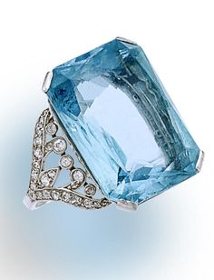 A belle époque aquamarine and diamond ring, circa 1910. Set with a rectangular-cut aquamarine, within a scrolling openwork old-cut diamond gallery and shoulders; aquamarine weighing approximately: 19.60 carats; estimated total diamond weight: 1.20 carats; mounted in platinum; size 6. Via Bonhams.