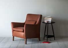 A club chair with a roomy cushioned seat. Available in high back and low back versions.