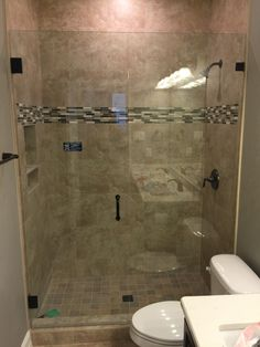 Frameless shower with door and fixed panel.  BM style handle and Oil Rubbed Bronze hardware finish.